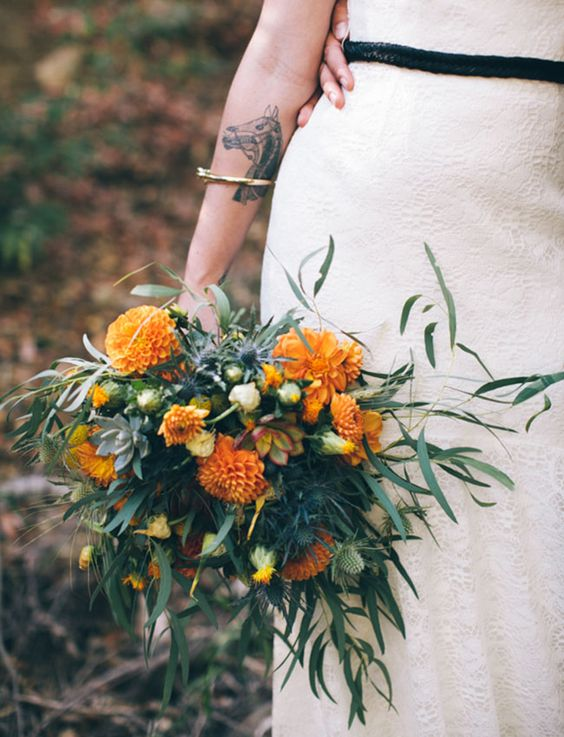 a whimsy two-toned bouquet of textural greenery and orange blooms plus some blue thistles