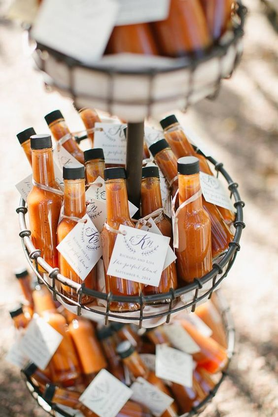 miniature bottles of hot sauce gathered in a basket and used as wedding favors with personalized tags