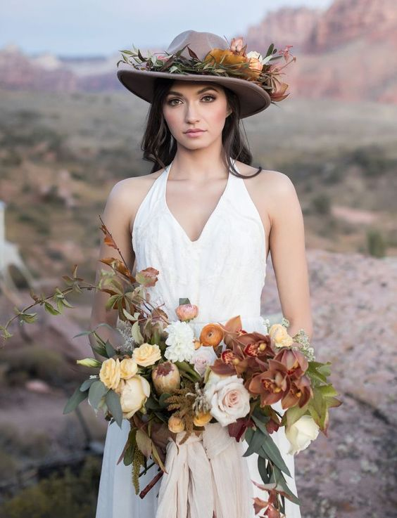 a brown hat topped with lush florals and foliage that match the bouquet