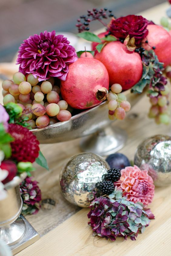 a chic fall centerpiece with grapes, pomegranates and dark dahlias in a silver bowl