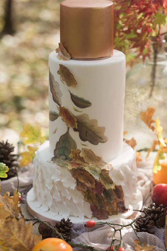 a chic wedding cake with a copper top and sugar leaves on all the layers for those who don't like naked