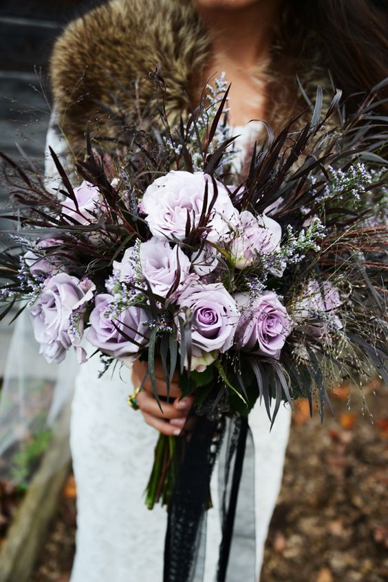 a lavender rose wedding bouquet with dark grasses for a haunted wedding