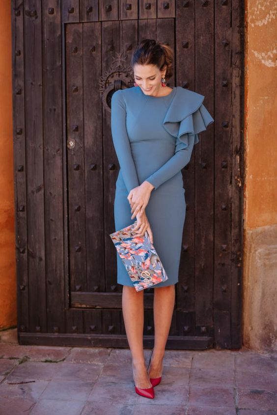 a muted blue knee dress with an asymmetric ruffle detail, a floral clutch and red shoes