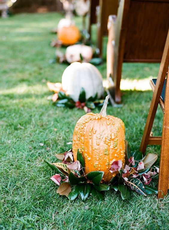 fall pumpkins placed on magnolia leaves are a great idea for a fall wedding, especially a southern one