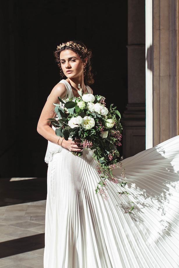 a Grecian-style bridal look with a casual pleated wedding dress and a gold leaf tiara