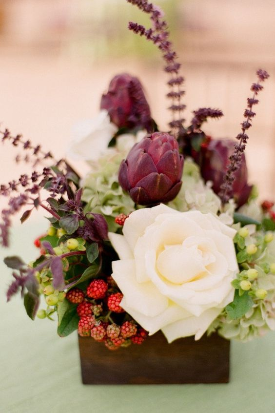a creative wedding centerpiece with veggies, berries and a large white rose for a contrast