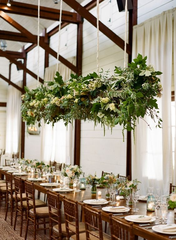 a hanging greenery and white bloom decoration over the reception and matching floral arrangements on the table