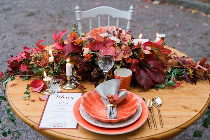 a lush wedding table runner done with bright blooms and fall leaves in jewel tones is a fantastic idea for the fall