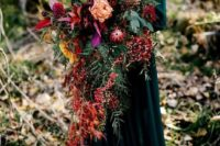 22 a super lush cascading wedding bouquet with lots of greenery, red leaves, berries and blooms of various shades
