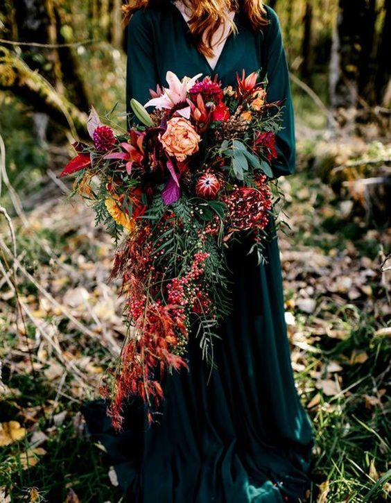 a super lush cascading wedding bouquet with lots of greenery, red leaves, berries and blooms of various shades