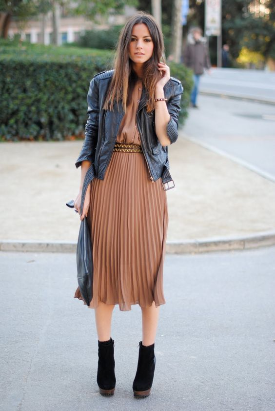 a taupe midi dress with a pleated skirt and a belt, a black leather jacket, a black clutch and black boots