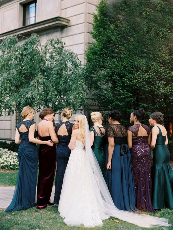 mismatching jewel tone bridesmaids' dresses in green, navy, burgundy and purple with embeliishments