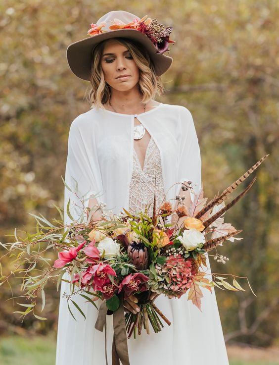 a fall boho bridal look with a trendy cape and a grey hat with lush blooms that match the bouquet