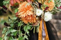23 a moody Halloween wedding bouquet with orange blooms, dark purple flowers and cascading greenery