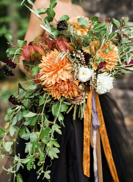 a moody Halloween wedding bouquet with orange blooms, dark purple flowers and cascading greenery