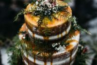 23 a naked fall wedding cake with greenery and berries and caramel drip is ideal for a woodland wedding