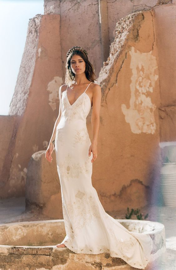 a slip wedding dress with gold lace appliques and a deep V-neckline plus a small train