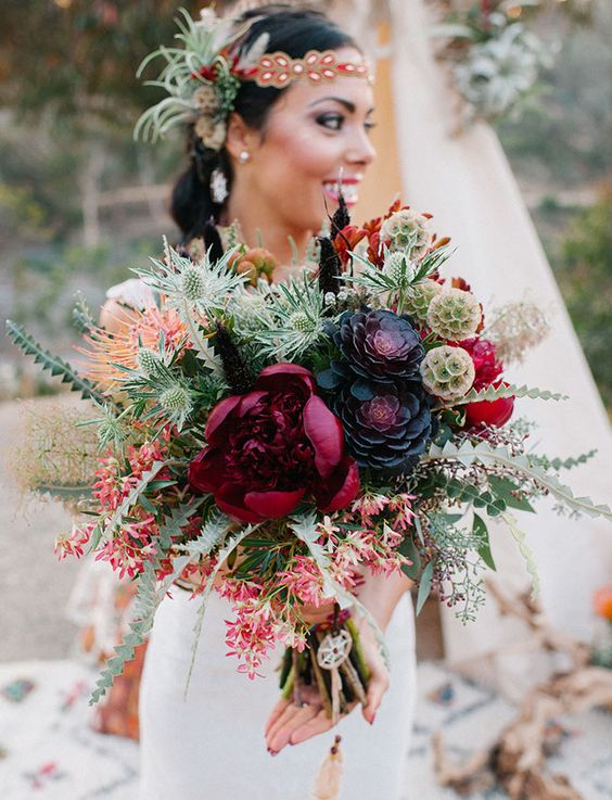 a super bold bouquet with burgundy, black and hot red blooms plus a lot of textural greenery