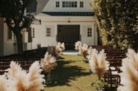23 pampas grass in glass vases to line up the aisle for a fall boho wedding
