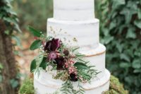 24 a semi naked wedding cake served on moss with dark floral and greenery decor for a refined touch
