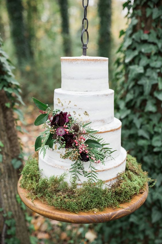 a semi naked wedding cake served on moss with dark floral and greenery decor for a refined touch
