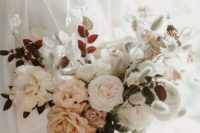 a soft pastel wedding bouquet with white and blush blooms plus herbs and orange ribbons for a delicate look