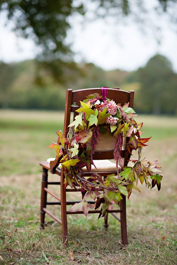 a wreath of burgundy dahlias and fall leaves is great for marking the couple's chairs