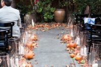24 pumpkins, fall leaves and candles in tall candle holders are all that you need to embrace the season