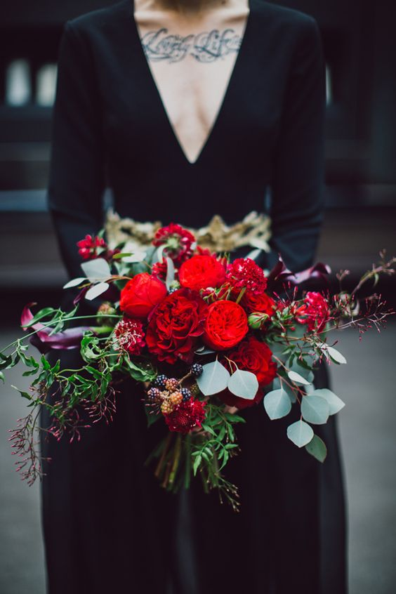 a super colorful Halloween wedding bouquet with red and dark purple blooms plus berries and greenery