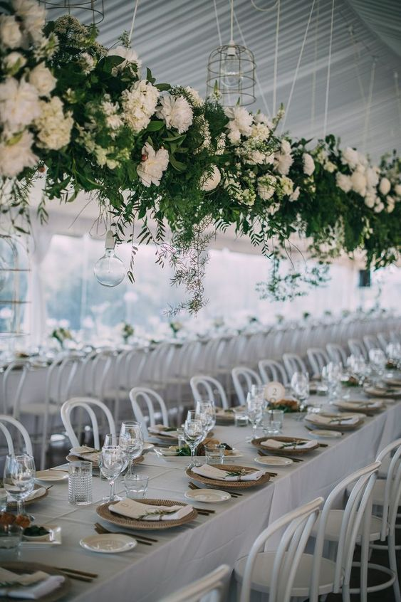 a super elegant suspended wedding decoration of greenery and white blooms makes centerpieces unnecessary