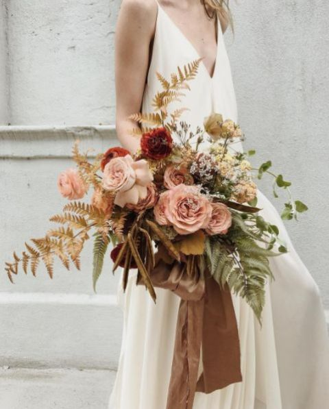 an organic pastel wedding bouquet with blush and rust blooms, gold and green leaves and some herbs for a delicate feel