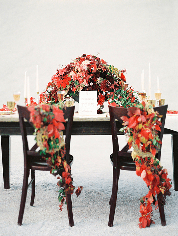 lush red and green fall leaf posies for the couple's chairs and a matching luxurious floral centerpiece