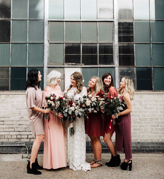 mismatching boho bridesmaids' dresses in red, pink, grey and dusty pink for a boho fall wedding