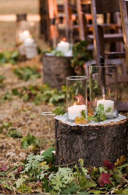 tree stumps with fall leaves and large candle holders are ideal for rustic or woodland weddings