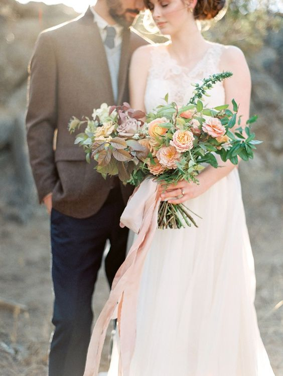 a delicate wedding bouquet with blush and lilac blooms plus foliage of various shades and pink ribbons