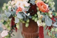 26 a soft wedding centerpiece of blush and red orange blooms plus pale greenery in a vintage urn