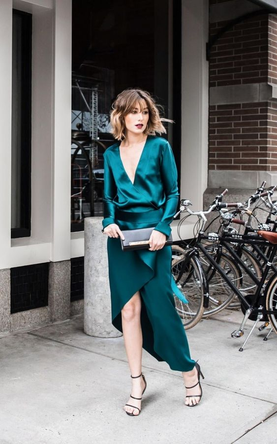 an emerald maxi dress with bell sleeves and a ruffled detail plus a plunging neckline, strappy shoes and a black clutch