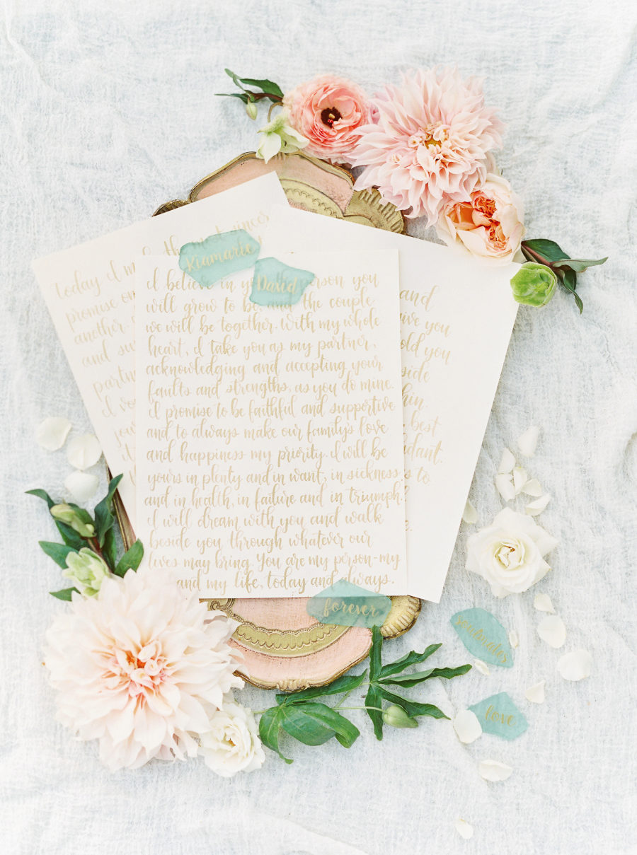 Here are wedding vows, chic gold calligraphy served on a tray with blooms