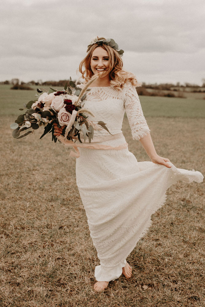 The bride was wearign a lace sheath boho dress with an illusion neckline