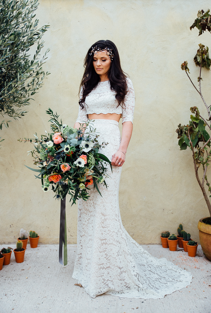 The bride was wearing a trendy two piece lace wedding dress with a crop top and long sleeves