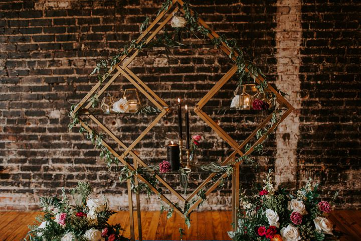 The cool wedding backdrop was a geometric one with shelves with candles and blooms covered with greenery