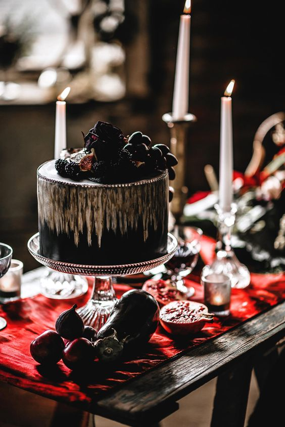 a black and gold wedding cake with berries and fruits on top and a dark rose for a luxurious Halloween wedding