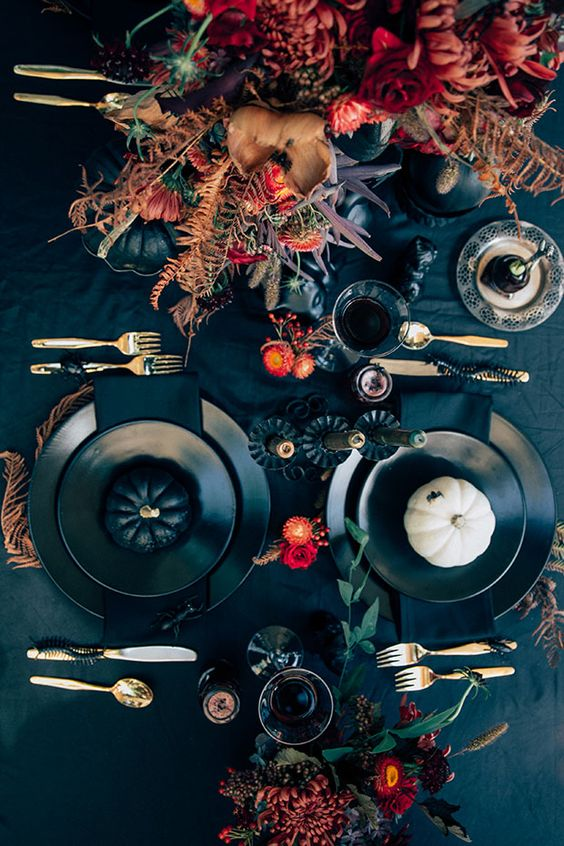 a black tablecloth, black pumpkins and bright flowers plus matte black plates