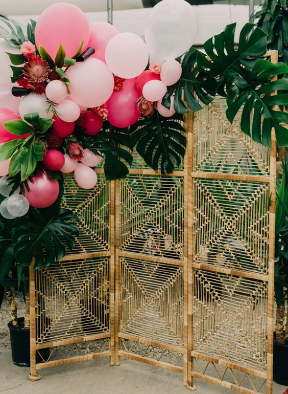 a boho tropical photo booth with a wicker backdrop decorated with tropical leaves and pink balloons