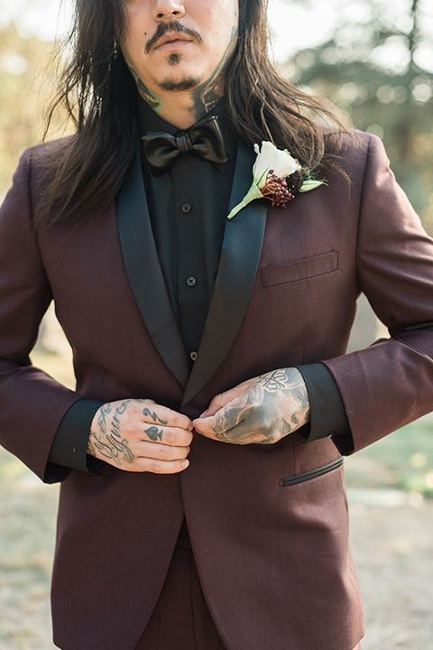a burgundy groom's tuxedo with a black bow tie plus a refreshing white boutonniere