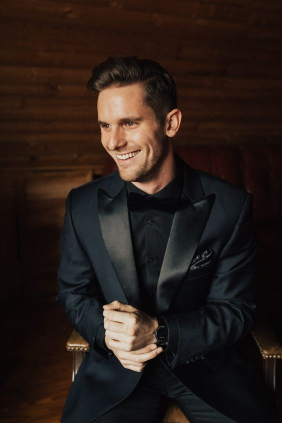 a classic black tuxedo with shiny lapels and a velvet bow tie, a black shirt