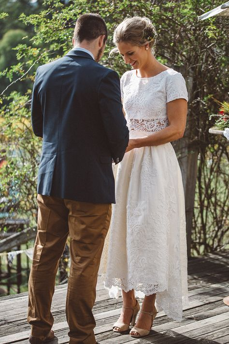 a romantic lace two piece wedding dress with a high low midi skirt and a crop top