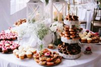 02 a simple dessert table decorated with candle lanterns and white blooms plus baby's breath