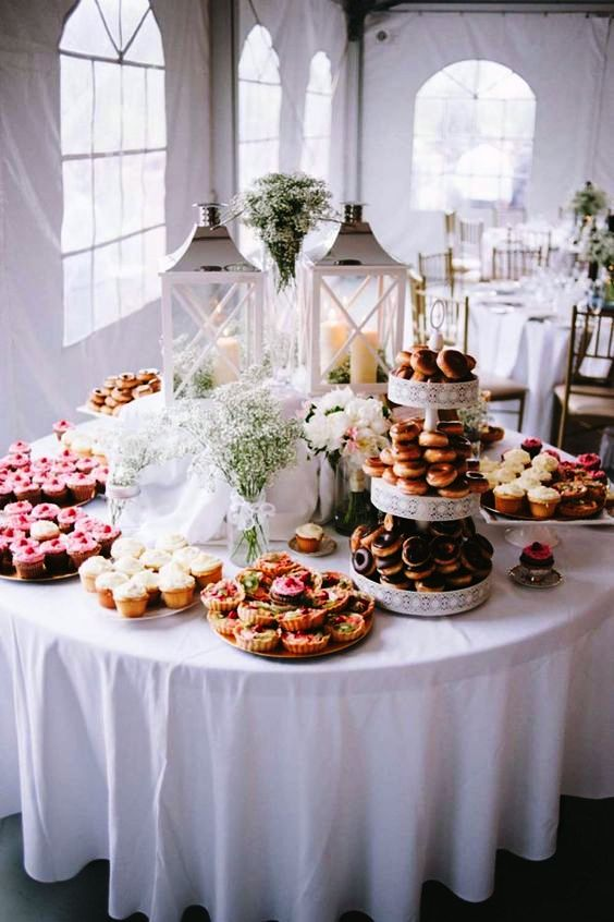 a simple dessert table decorated with candle lanterns and white blooms plus baby's breath