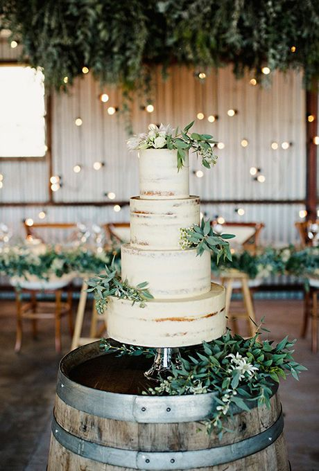 the cake is placed on a barrel with some greenery not far from the reception